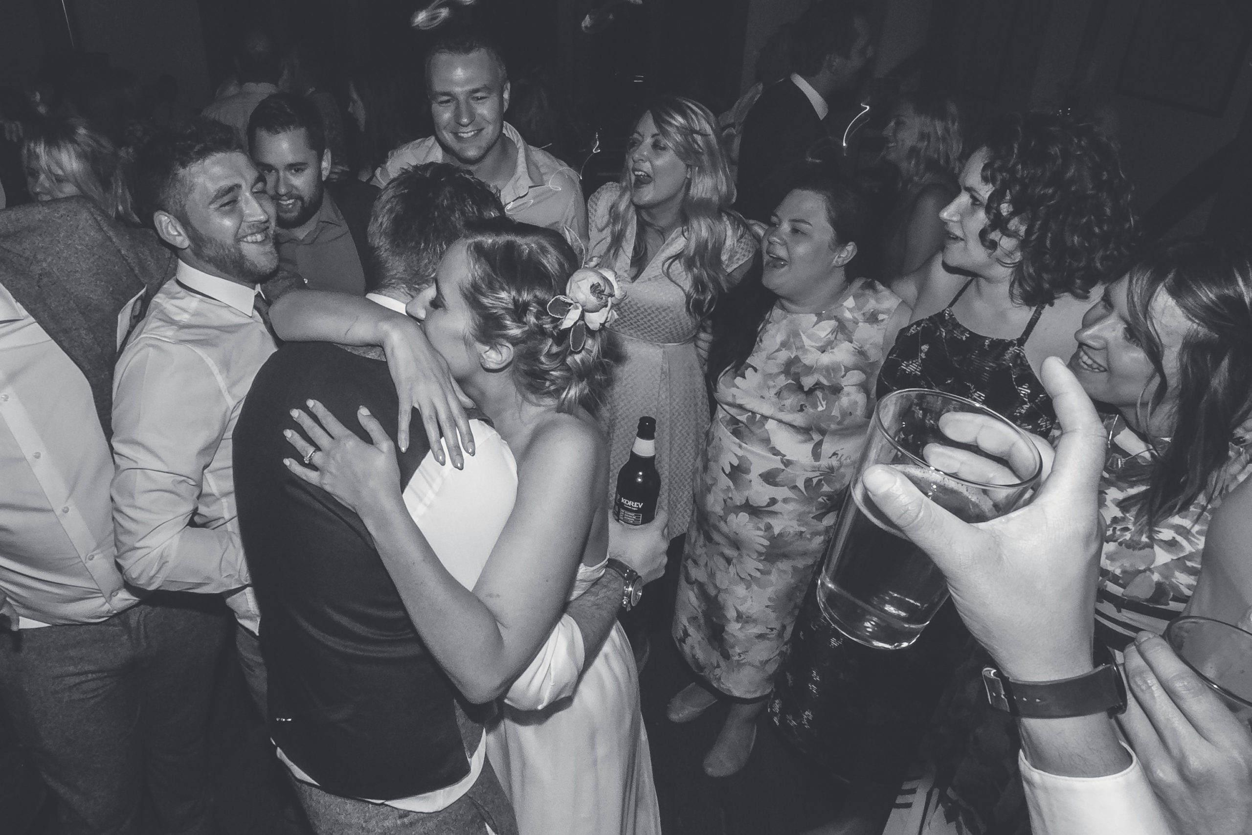 Couples embrace at the end of a wedding