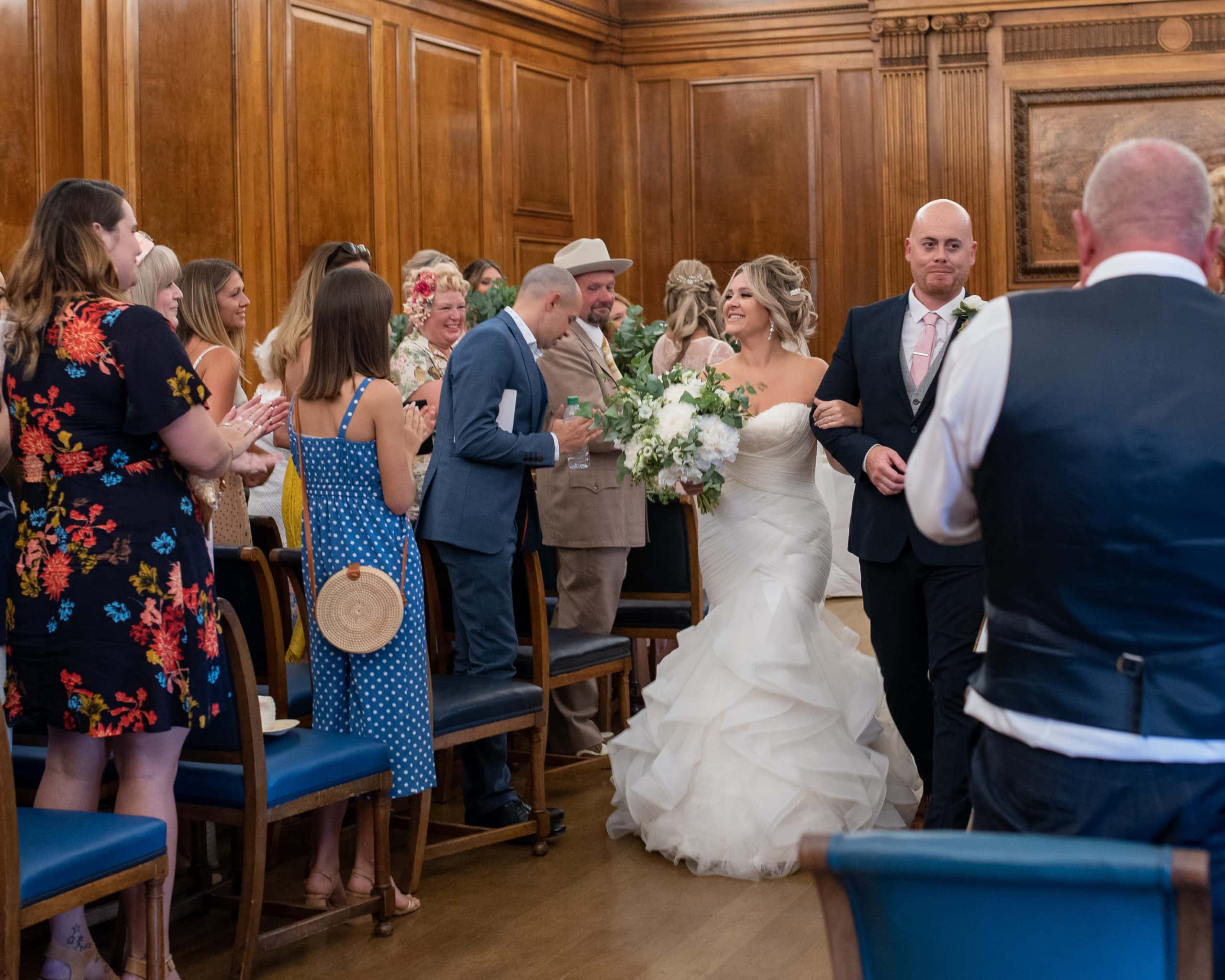 Bride and groom walking out of their Nottingham Council House wedding