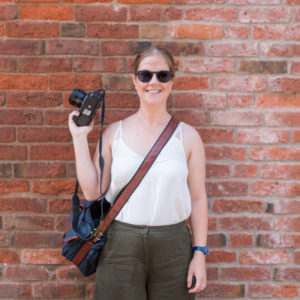Amy, Nottingham wedding photographer, stood in front of awall with her camera