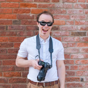 Dave Fuller, Nottingham Wedding Photographer, standing in front of wall